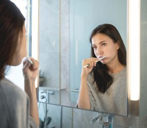 Woman brushing her teeth in mirror - Tooth Extraction Vallejo, CA