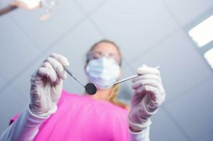 Dentist standing above patient with tools - Dental Anesthesia Vallejo, CA