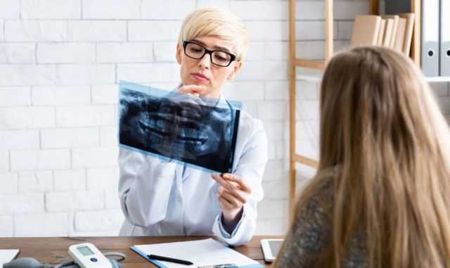 Female Doctor looking for periodontal disease on a patient's x-ray results - Rotary Way, CA