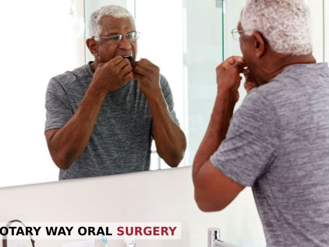 Older man flossing teeth in front of the mirror - Rotary Way, CA
